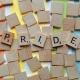 Scrabbelstenen die gezamenlijk het woord 'PRIDE' vormen
