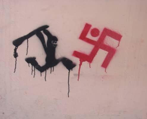 Graffiti van een poppetje dat achter een hakenkruis aanjaagt