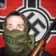 Een gewapende neonazi voor een vlag met een hakenkruis