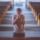 Een biddende man in een kerk